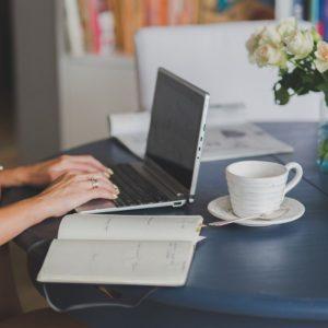Händer som skriver på en laptop, en uppslagen bok och en kopp kaffe illustrerar flitiga händer som du kan hyra in via en redaktörstjänst.