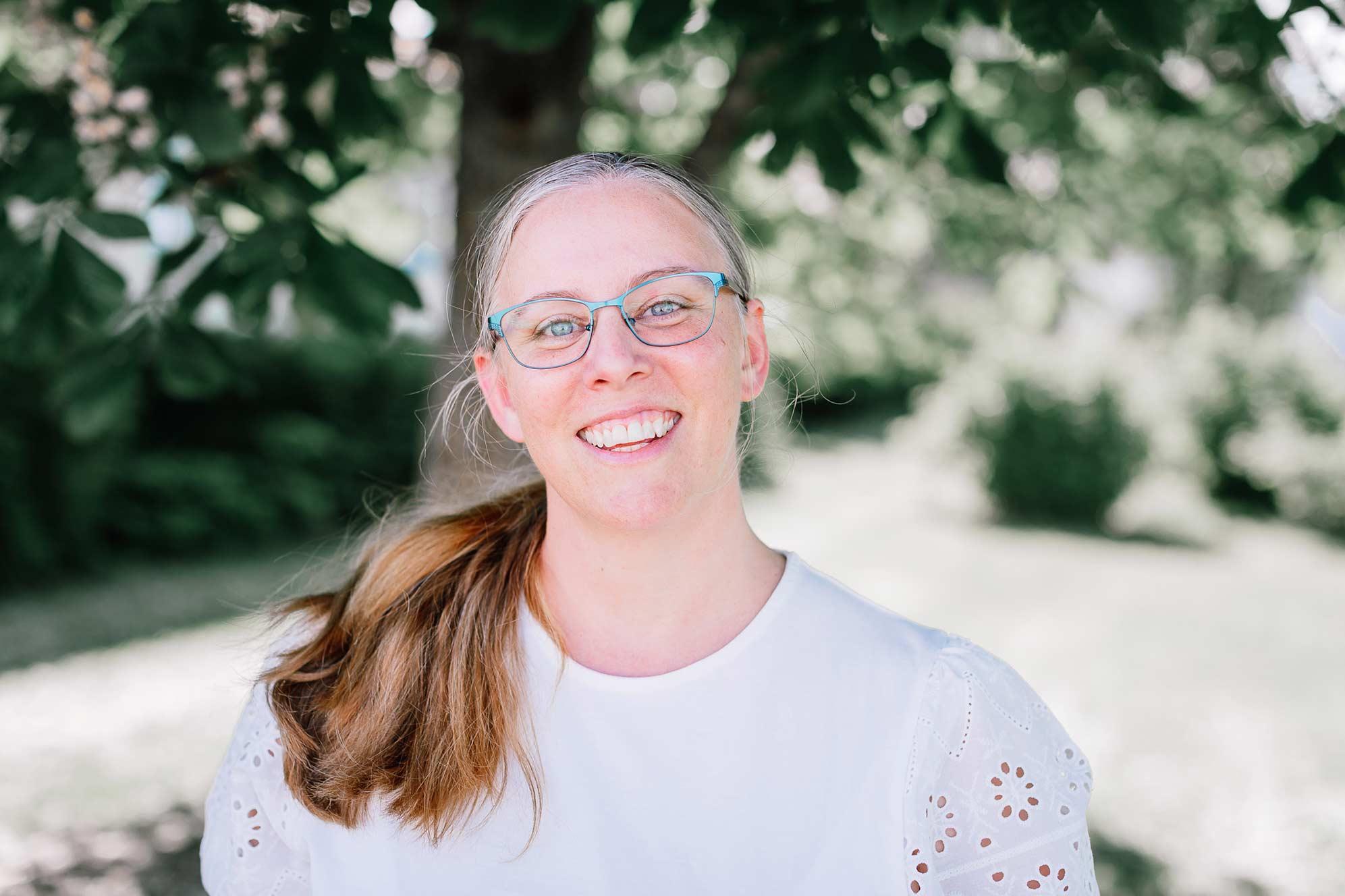 Maria Åkerblom, ägare av kommunikationsbyrån Åkerblom Kommunikation i Nyköping, står under ett träd och ser glad och välkomnande ut.