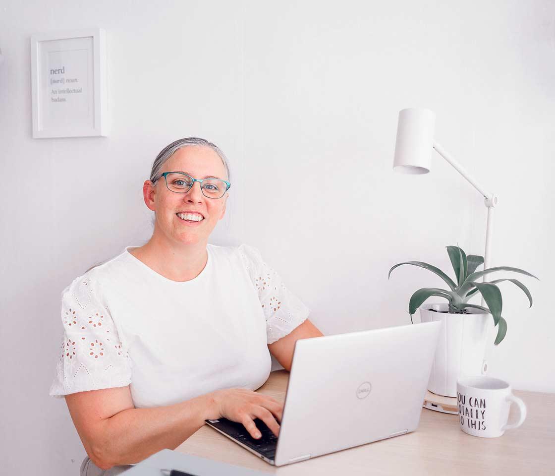 Maria Åkerblom sitter vid en dator, Hon skriver på tangentbordet och tittar upp och ser glad ut.